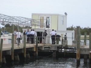 Onlookers observe Lozman houseboat moored at Riviera Beach docks.