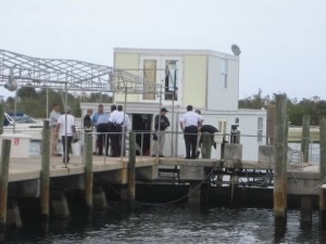 Onlookers observe Lozman houseboat moored at Riviera Beach docks.
