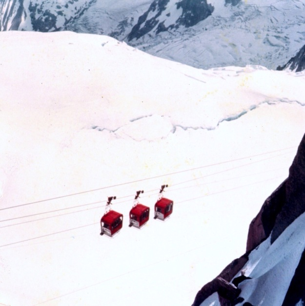 Is three gondola transporting skiers to various stops on Mount Blanc, Chamonix, France? Or is this three maraschino cherries dangling over several scoop of vanilla ice cream?