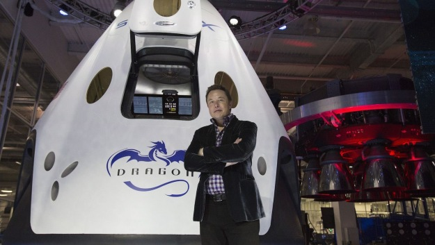 Billionaire Elon Musk stands in front of personal space capsule.