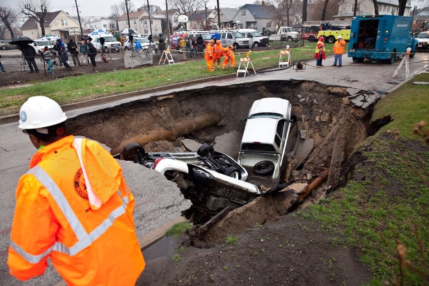 Large sink hole with auto under asphalt in multi-family residential area.