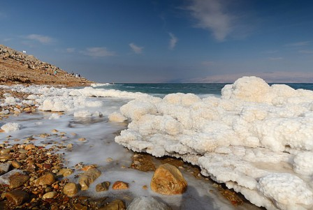 Dead Sea beach with accumulated sea salt along the edges between the Sea and the beaches.