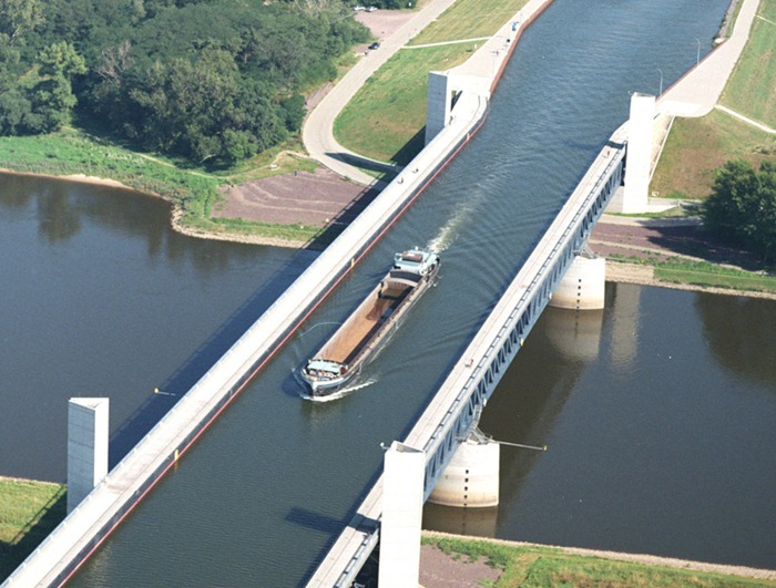 Concrete water bridges over a perpendicular water bridge with a hopper filled with  gran